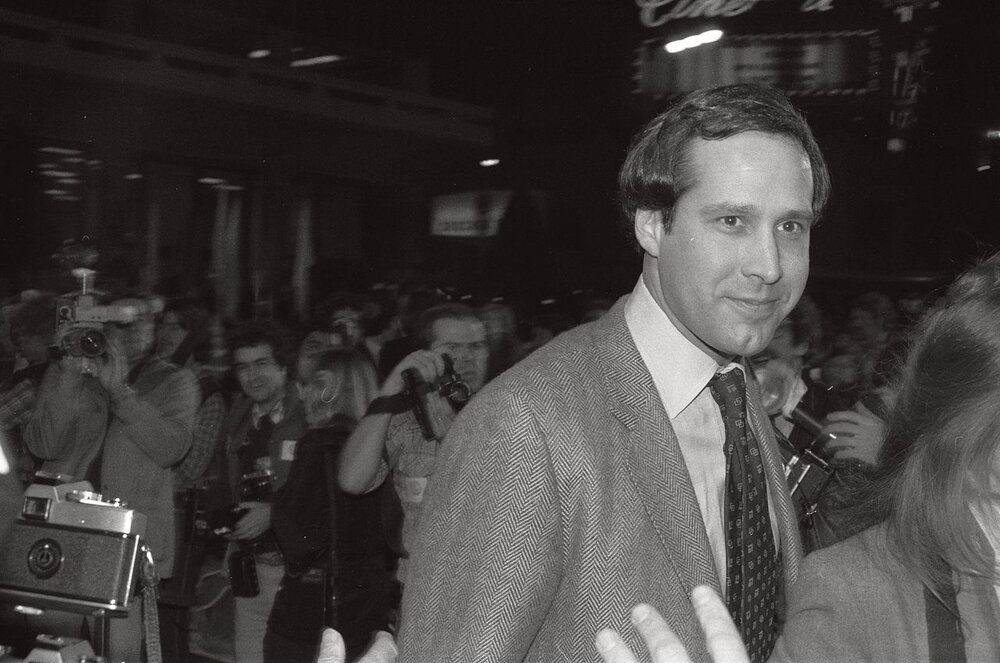 By photo by Alan Light, CC BY 2.0,  https://commons.wikimedia.org/w/index.php?curid=1319758  Chevy Chase at the premiere for Seems Like Old Times, three years before becoming Clark Griswold.